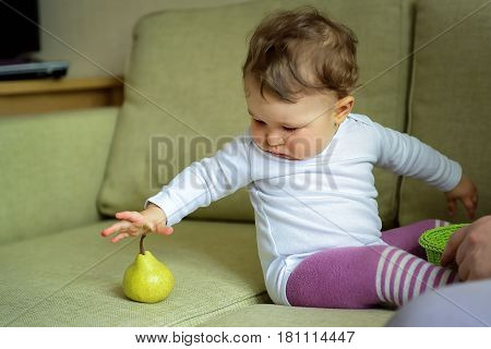Cute baby girl plays with fruit at home. The one-year child wants to grab a pear.
