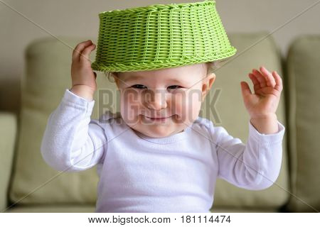 Cheerful baby puts a fruit dish on his head. One-year-old child plays at home.