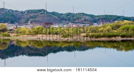 Landscape of river with a small town nestled in a valley and the trees and mountain reflection on the calm waters