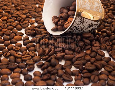 Scattered coffee beans with inverted oriental cup over white background