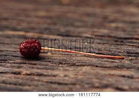 A small wild berry is on a wooden bench.