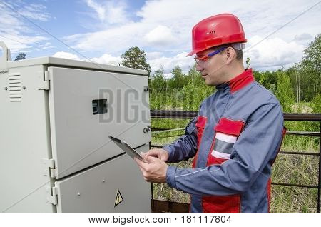 Electrician builder engineer checking data from control panel holding tablet computer. Blue sky and forest background. Outdoor shot.