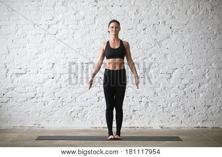 Middle aged yogi attractive smiling woman practicing yoga concept, standing in mountain exercise, Tadasana pose, working out, wearing black sportswear top and pants, full length, white loft background