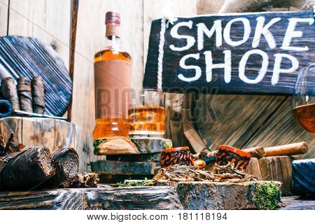 Details of smoke shop showcase in rustic style. Wooden signboard with text hanging over oak barrel. Various smoking pipes, tobacco, cigars and smokers alcohol on natural wood counter