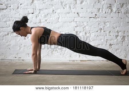 Middle aged yogi attractive woman practicing yoga concept, standing in Push ups, press ups exercise, phalankasana, Plank pose, working out wearing black sportswear, full length, white loft background