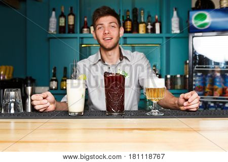 Young handsome Barman offers exotic sweet cocktails in restaurant. Professional bartender at work in night club bar made refreshing drinks. Selective focus on glasses of cream soda and berry mix