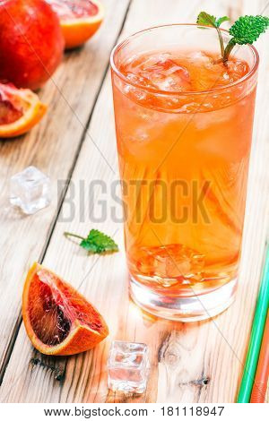 Refreshing iced drink in high glass and blood sicilian oranges on raw wood table