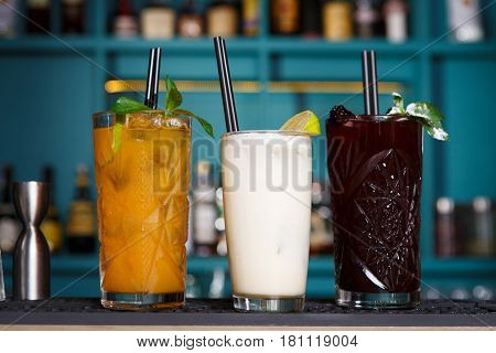 Closeup of three creative sweet exotic alcohol party cocktails in restaurant at bar background. Glasses on bar table, refreshing drinks with straws.