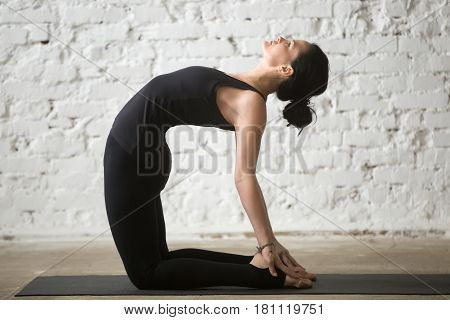 Young yogi attractive woman practicing yoga concept, stretching in Ustrasana exercise, Camel pose, working out, wearing sportswear, black tank top and pants, full length, white loft background