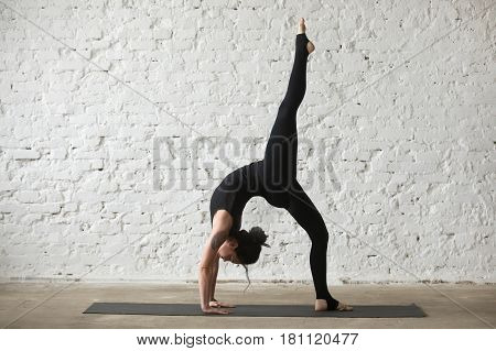 Young yogi attractive woman practicing yoga concept, standing in One legged Wheel exercise, Bridge pose, working out, wearing sportswear, black tank top and pants, full length, white loft background