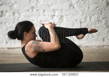 Young yogi attractive woman practicing yoga concept, stretching in Knees to Chest exercise, Apanasana pose, working out, wearing sportswear, black tank top and pants, full length, loft background