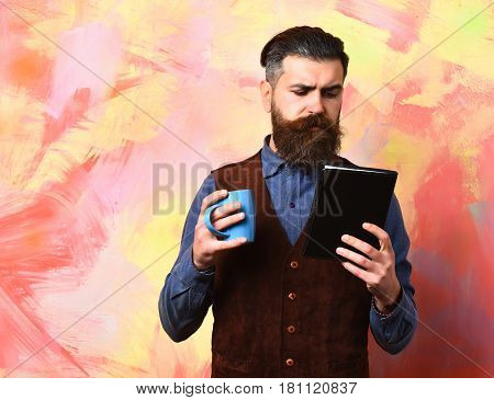 Bearded man long beard. Brutal caucasian serious hipster with moustache holding blue coffee cup and black notebook in vintage shirt and leather vest on colorful studio background