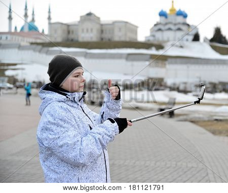 A boy does selfie on the phone with a self-stick against the backdrop of the Kazan Kremlin, Russia