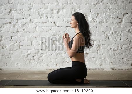 Middle aged yogi woman practicing yoga concept, sitting in seiza exercise, vajrasana pose, working out, wearing sportswear, black tank top and pants, full length, white loft background, side view