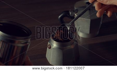 Close up of man's hand pouring coffee in a geyser