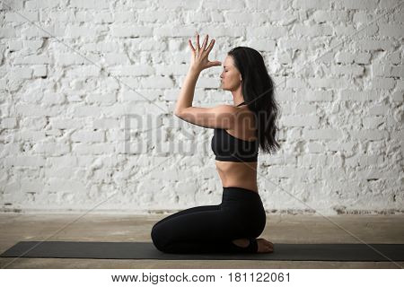 Mid aged yogi attractive woman practicing yoga concept, sitting in seiza exercise, vajrasana pose, namaste, working out, wearing black sportswear bra and pants, full length, white loft background