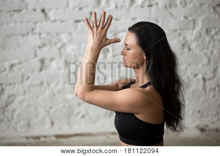 Portrait of middle aged yogi attractive woman practicing yoga concept, making namaste gesture with her eyes closed, working out, wearing black sportswear bra, close up, white loft background