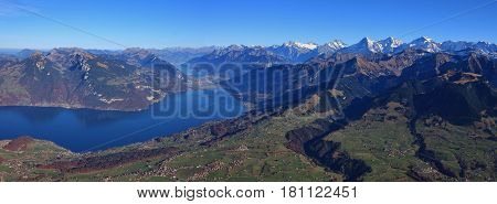 Beautiful autumn day in the Bernese Oberland. Villages Aeschi and Aeschiried. Lake Thunersee. Distant view of Eiger Monch and Jungfrau.