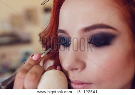Make-up artist does makeup to the red-haired girl in studio. Smoky eyes.