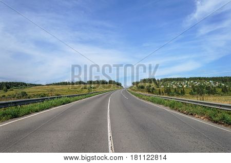 Asphalt road through the hill near the small village green woods and meadows around sunny summer day
