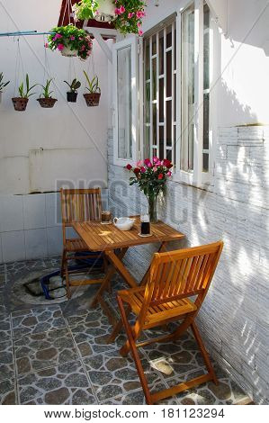Glass of black coffee & brown coffee on wooden table with couple of chairs and rose pot under window in the yard