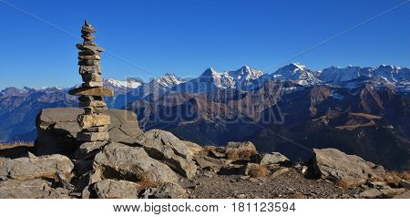 Cairn on top of mount Niesen. View of the famous mountains Eiger Monch and Jungfrau. Autumn day in the Swiss Alps.