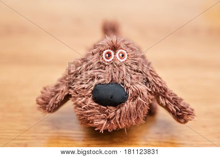 Soft toy dog close-up on a wooden table
