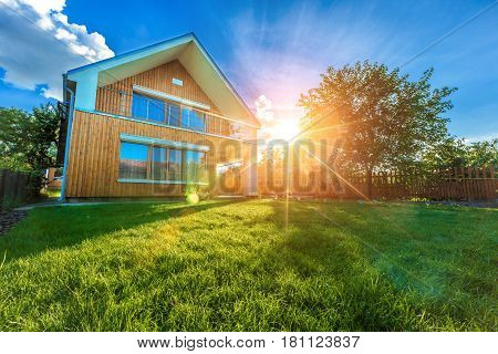 Modern summer cottage against a blue sky in the summer garden. Sunny day