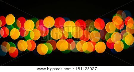 Brilliant colorful circle bokeh made by blurry colorful lights. Isolated on black.