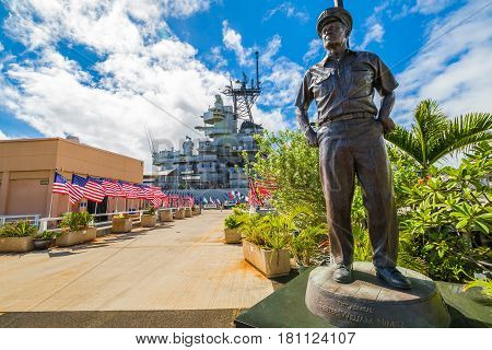HONOLULU, OAHU, HAWAII, USA - AUGUST 21, 2016: bronze statue of Admiral Chester W. Nimitz at battleship USS Missouri in Pearl Harbor Memorial with American flags. Commander in chief of Pacific Fleet.