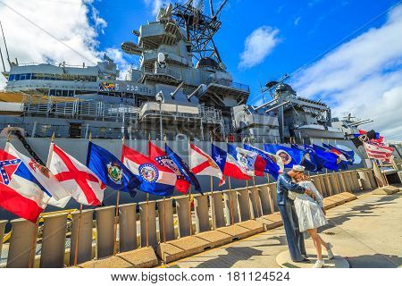 HONOLULU, OAHU, HAWAII, USA - AUGUST 21, 2016: Sailor and nurse in NY Times Square 1945 victory kiss statue at Missouri Memorial with flags at Pearl Harbor base.