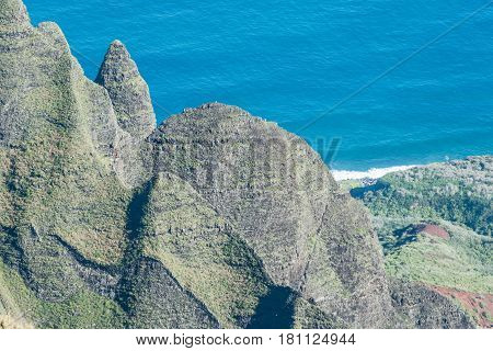 Lush Structures: lush, rock formations along the Napali Coastline, and partial view of the ocean, from the Kalalau Lookout, on Kauai