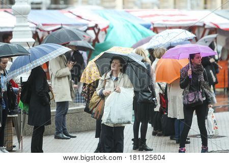 People With Umbrellas On Square