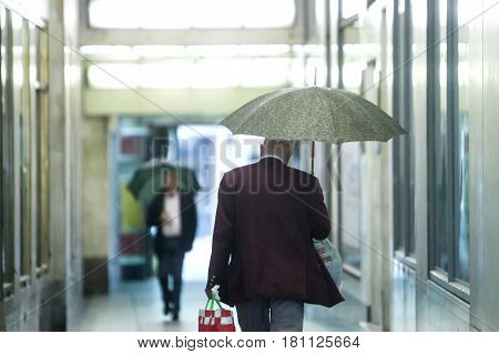 Senior Adults With Umbrellas In Passage
