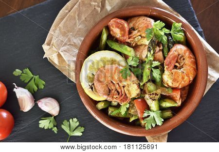 Fresh jumbo shrimps and green asparagus, delicious dish or meal, close-up shot. Spanish Tapas, high angle view.