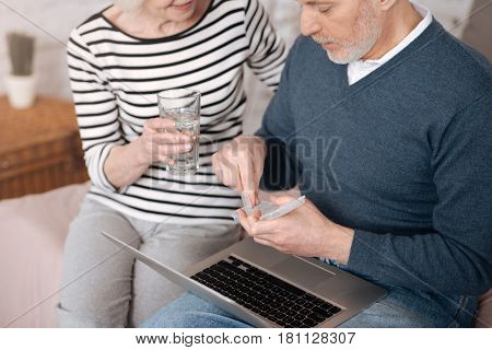 Supporting each other. Top view of elderly man going to take some pills from case while his wife holding water glass for him.