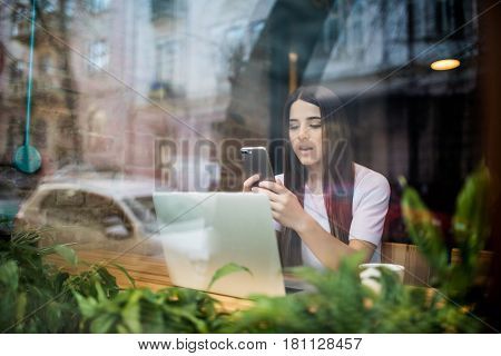 View Through Window Of A Charming Girl With Cell Phone In Hands Is Thinking What To Write In Text Me