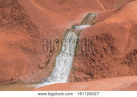Magical Falls: close up of a small water flowing over red dirt mounds, on Kauai