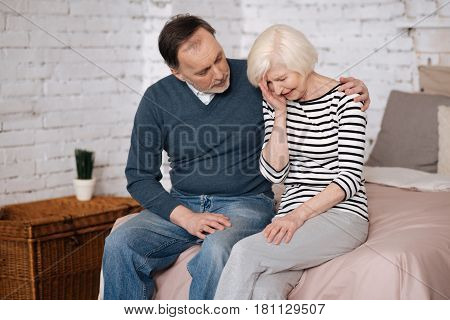 Everything will be good. Old man is hugging and supporting his crying wife while sitting on bed at home.