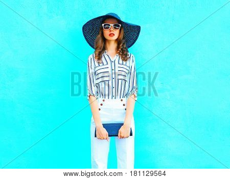 Fashion Young Woman Wearing A Straw Hat, White Pants With A Handbag Clutch Over Colorful Blue Backgr