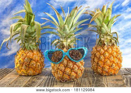 pineapple on rustic wood wearing heart shaped sunglasses