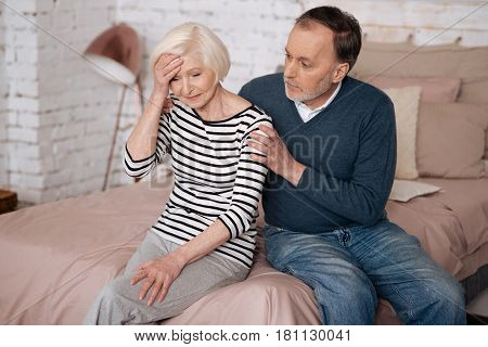 Bad news. Senior depressed lady is sitting on bed near her husband and touching her forehead with hand.