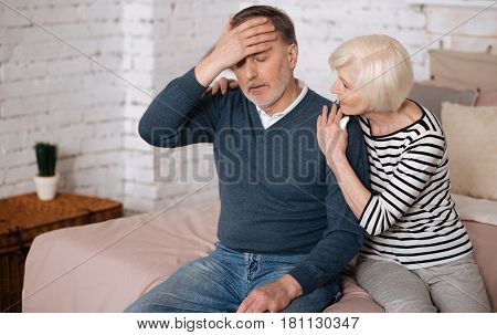 I feel bad. Elderly ill man is touching his forehead and his senior wife is trying to support him.