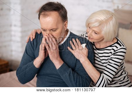 Suffering from allergy. Senior wife supporting her elderly husband covering his face while sneezing.