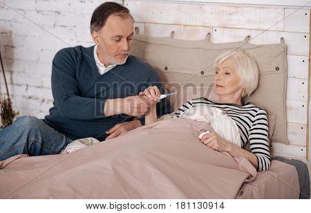 Take it. Senior handsome man is giving thermometer to his elderly ill wife lying on bed covered with warm blanket.
