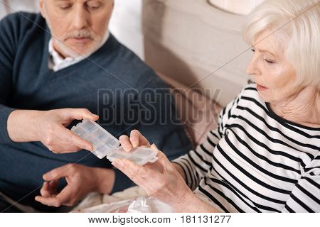 Thank you. Top view of elderly man holding transparent pills case while his ill wife is taking pill from it.