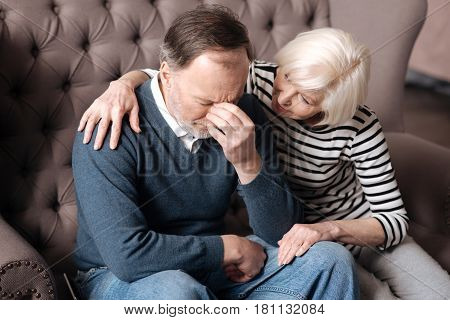 Please calm down. Elderly woman is sitting and embracing her husband in depression at home.