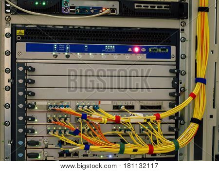 The central router with a plurality of optical cables in datacenter server room. Multiple servers in the rack