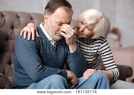 Do not worry. Senior lady embracing her depressed husband while sitting on couch at home.