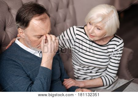 You will handle it. Close up top view of elderly man touching his nasal bridge while having strong headache near his supportive wife.